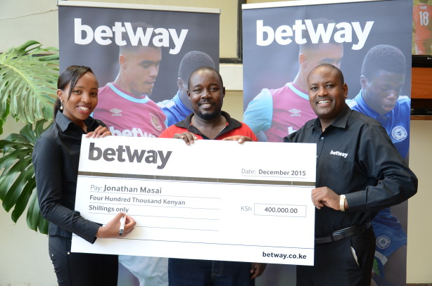 Jonathan Maasai (centre), an employee of Kenya Power, receives a dummy cheque equivalent of Ksh400,000 from Betway marketing assistant, Hellen Murathimi (left) and business development manager, Jacob Mbuthia in Nakuri after winning Betway Jackpot bonus